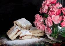 Τα σπιτικά γλυκά μπισκότα με τη μαρμελάδα, που ψεκάζεται με την κονιοποιημένη ζάχαρη, κλείνουν επάνω στοκ εικόνες