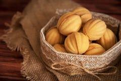 Τα σπιτικά διαμορφωμένα μπισκότα καρύδια με την κρέμα έβρασαν συμπυκνωμένος milkt στον ξύλινο πίνακα στοκ φωτογραφίες