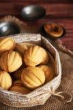 Τα σπιτικά διαμορφωμένα μπισκότα καρύδια με την κρέμα έβρασαν συμπυκνωμένος milkt στον ξύλινο πίνακα στοκ εικόνα