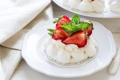 Τα σπιτικά μικρά κέικ μαρέγκας pavlova φραουλών με το mascarpone αποβουτυρώνουν και φρέσκα φύλλα μεντών Στοκ Φωτογραφία