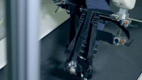 Τα σταθεροποιηθε'ντα πόδια ενός με ειδικές ανάγκες ατόμου περπατούν αργά κατά μήκος του εξοπλισμού rehab απόθεμα βίντεο