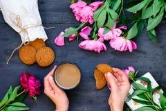Τα στενά επάνω θηλυκά χέρια τοπ άποψης που κρατούν την κούπα του καφέ και των μπισκότων που περιβάλλονται με τα peonies ανθίζουν  Στοκ Φωτογραφία