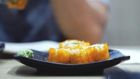 Τα στενός-Upman χέρια βάζουν το wasabi στο ρόλο με ένα δίκρανο και βυθίζουν το ρόλο στη σάλτσα σόγιας 3840x2160 απόθεμα βίντεο