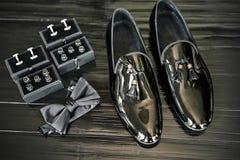 Τα στιλπνά μαύρα παπούτσια, κουμπιά πουκάμισων στο σύνολο παραθύρων, μαύρος δεσμός τόξων στο μαύρο ξύλινο πάτωμα - τοπ άποψη, κλε στοκ φωτογραφία