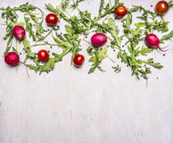 Τα συστατικά για το μαγείρεμα του χορτοφάγου μαρουλιού, ραδίκια, ντομάτες κερασιών, arugula σχεδίασαν το άσπρο ξύλινο αγροτικό υπ Στοκ Εικόνα