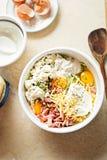 Τα συστατικά frittata κέικ κολοκυθιών ανάμιξαν το άσπρο κύπελλο - αυγά, αλεύρι, ξυμένο κολοκύθι, μπέϊκον, φέτα, mascarpone και τυ Στοκ Φωτογραφίες
