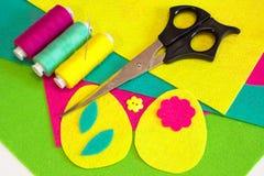 Τα σχέδια αυγών Πάσχας θέτουν, κουμπιά λουλουδιών, χρωματισμένα νήματα καθορισμένα, ψαλίδι, επίπεδα αισθητά κομμάτια Πώς να κάνει Στοκ φωτογραφία με δικαίωμα ελεύθερης χρήσης