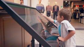 Τα σύγχρονα έξυπνα παιδιά χρησιμοποιούν τις νέες σύγχρονες τεχνολογίες για τις πληροφορίες αναζήτησης για τη θέση του καταστήματο φιλμ μικρού μήκους