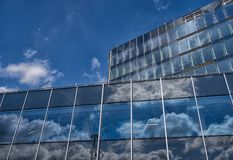 Τα σύννεφα και ο ουρανός απεικόνισαν στα πλακάκια γυαλιού σχεδόν του ολοκληρωμένου κτηρίου, Woking, Surrey στοκ εικόνες με δικαίωμα ελεύθερης χρήσης
