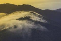 Τα σύννεφα καλύπτουν τα βουνά Στοκ Φωτογραφία
