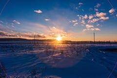 Τα σύνολα ήλιων πίσω από τα βουνά και χρωματίζουν τα σύννεφα το χειμώνα, Altai, Ρωσία στοκ φωτογραφίες
