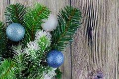 Τα σύνορα από τα τυλιγμένα χριστουγεννιάτικα δώρα, δέντρο γουνών διακλαδίζονται, κόκκινα μούρα στο ηλικίας ξύλινο υπόβαθρο Στοκ Εικόνα