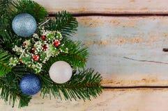 Τα σύνορα από τα τυλιγμένα χριστουγεννιάτικα δώρα, δέντρο γουνών διακλαδίζονται, κόκκινα μούρα στο ηλικίας ξύλινο υπόβαθρο Στοκ Εικόνες