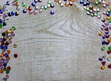 Τα σύνορα πλαισίων του ζωηρόχρωμου ποτηριού διακοσμούν τις καρδιές στο ξύλινο υπόβαθρο με χάντρες Στοκ Φωτογραφία