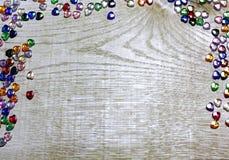 Τα σύνορα πλαισίων του ζωηρόχρωμου ποτηριού διακοσμούν τις καρδιές στο ξύλινο υπόβαθρο με χάντρες Στοκ εικόνα με δικαίωμα ελεύθερης χρήσης