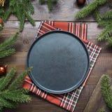 Τα σύνορα τροφίμων Χριστουγέννων με το μαύρο πιάτο, οι κλάδοι, και το κόκκινο ντεκόρ στον ξύλινο πίνακα Διάστημα για το κείμενο Τ στοκ φωτογραφία με δικαίωμα ελεύθερης χρήσης