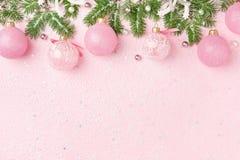 Τα σύνορα Χριστουγέννων του νέου έτους διακοσμούν το έλατο στο ρόδινο υπόβαθρο στοκ εικόνα