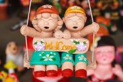 Τα ταϊλανδικά παιδιά αγαλμάτων κρατούν το σημάδι που είστε ευπρόσδεκτοι Στοκ Εικόνα