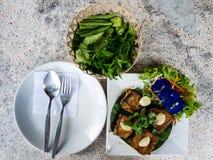 Τα ταϊλανδικά τρόφιμα, προετοιμάζονται για τρώνε το δίκρανο και το πιάτο κουταλιών με τα τηγανισμένα ψάρια και τα λαχανικά Στοκ Εικόνα