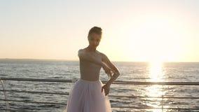 Τα τεντώματα Ballerina στην παραλία, χαριτωμένο χορευτικό βήμα μπαλέτου άσκησης κοριτσιών, δίνουν τις ασκήσεις Ακτίνες ήλιων πρωι φιλμ μικρού μήκους
