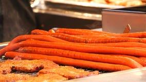 Τα τεράστιες μακριές κόκκινες λουκάνικα μισό-μετρητών και οι μπριζόλες κρέατος με τον ατμό πέρα από τους ψήνουν στην αγορά Χριστο απόθεμα βίντεο