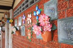 Τα τεχνητά λουλούδια διακοσμούν στο τουβλότοιχο Στοκ Εικόνες