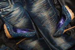 Τα τζιν και τα παπούτσια τζιν με τα κρύσταλλα στο μαύρο μετάξι Στοκ Εικόνα