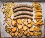 Τα τηγανισμένα λουκάνικα στο δίσκο ψησίματος με τα ψημένες μήλα, τα κρεμμύδια και τη φρυγανιά κουλουριών αλυσίβας, τοπ άποψη, κλε Στοκ φωτογραφία με δικαίωμα ελεύθερης χρήσης