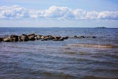 Τα τιτιβίσματα πετρών κορυφογραμμών από το νερό στον κόλπο θάλασσας, μεγάλα κύματα της παλίρροιας, σωρείτης καλύπτουν στον ορίζον Στοκ Εικόνες