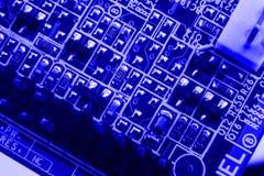 Τα τμήματα ηλεκτρονικής στη σύγχρονη μητρική κάρτα υπολογιστών PC που το μπλε υπόβαθρο κλείνει τη μακροεντολή απομονώνουν Στοκ Εικόνες