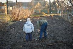 Τα του χωριού παιδιά σκάβουν έναν φυτικό κήπο την άνοιξη Στοκ φωτογραφία με δικαίωμα ελεύθερης χρήσης
