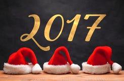 Τα τρία κόκκινα καπέλα Santa στο ξύλινο υπόβαθρο Στοκ Εικόνες