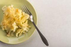 Τα τραγανά μακαρόνια με το τυρί έξυσαν στο φούρνο, που εξυπηρετήθηκε στο πιάτο επάνω από το άσπρο μαρμάρινο υπόβαθρο Στοκ φωτογραφία με δικαίωμα ελεύθερης χρήσης