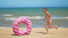 Τα τρεξίματα αγοριών κατά μήκος της παραλίας με ρόδινο διογκώσιμο doughnut, το κυλούν κατά μήκος της άμμου στα πλαίσια της θάλασσ απόθεμα βίντεο