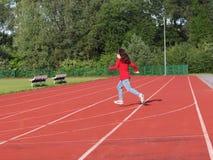 Τα τρεξίματα κοριτσιών πέρα από treadmill στο στάδιο Τεχνητό επίστρωμα για το τρέξιμο και τα αθλητικά θεάματα Αθλητισμός και αθλη στοκ εικόνες με δικαίωμα ελεύθερης χρήσης