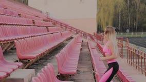 Τα τρεξίματα κοριτσιών στο στάδιο μεταξύ των καθισμάτων, που εκπαιδεύουν στο καθαρό αέρα απόθεμα βίντεο