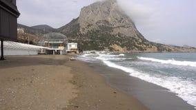 Τα τρεξίματα κυμάτων θάλασσας στην εγκαταλειμμένη ακτή χαλικιών της Μαύρης Θάλασσας Νεφελώδης ημέρα άνοιξη στο χωριό Novy Svet στ φιλμ μικρού μήκους