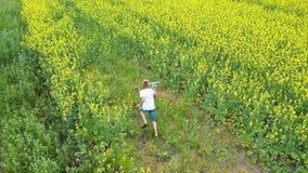 Τα τρεξίματα τύπων μέσω του τομέα λουλουδιών, που κρατά ένα αεροπλάνο Ηλιόλουστη θερινή ημέρα απόθεμα βίντεο