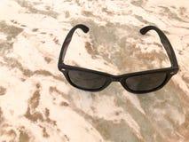 Τα τριαδικά πλαστικά γυαλιά ηλιοψημένων με το μαύρο γυαλί και τα τόξα βρίσκονται σε μια καφετιά άμμος-χρωματισμένη ελαφριά πέτρα  στοκ φωτογραφία με δικαίωμα ελεύθερης χρήσης