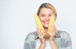 Τα τρόφιμα φέρνουν την ευτυχία o Γυναικών άσπρο υπόβαθρο σπαδίκων καλαμποκιού λαβής κίτρινο Λαβή κοριτσιών συγκομιδών καλαμποκιού στοκ φωτογραφία με δικαίωμα ελεύθερης χρήσης