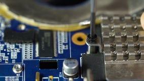 Τα τσιμπιδάκια εκμετάλλευσης χεριών σε ετοιμότητα lap-top screwA που κρατά ένα κατσαβίδι εγκαθιστούν ή επισκευάζουν τα τμήματα υπ απόθεμα βίντεο