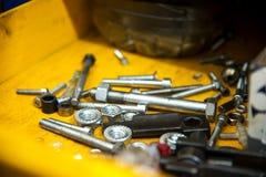 Τα τυχαία διεσπαρμένα μπουλόνια και τα καρύδια προορισμού καυσίμων βρίσκονται σε ένα κίτρινο κιβώτιο Στοκ Φωτογραφία