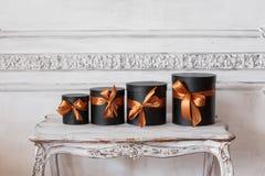 Τα τυλιγμένα μαύρα κουτιά δώρων με τις κορδέλλες ως χριστουγεννιάτικα δώρα σε έναν άσπρο τοίχο επιτραπέζιας πολυτέλειας σχεδιάζου Στοκ Εικόνες