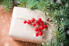 Τα τυλιγμένα χριστουγεννιάτικα δώρα, δέντρο γουνών διακλαδίζονται, κόκκινα μούρα στο αγροτικό ξύλινο υπόβαθρο Συρμένη επίδραση χι Στοκ Φωτογραφίες