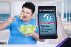 Τα υγιή ψηφίσματα app με το άτομο τρώνε τη σαλάτα Στοκ Εικόνα