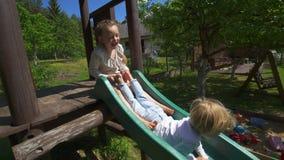 Τα υπερενεργητικά παιδιά γλιστρούν κάτω στην παιδική χαρά Παιχνίδι και γέλιο παιδιών Φορητός απόθεμα βίντεο