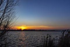 Τα υπολείμματα του μαργαριταρένιου ουρανού είναι ορατά και χρώματα ο ουρανός επάνω από τα plas Zoetermeerse λιμνών σε Zoetermeer, στοκ φωτογραφία