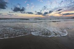 Τα υψηλά κύματα με τον αφρό διαδίδουν στην άμμο στην ακτή που το φως του απίστευτου ηλιοβασιλέματος απεικονίζει στη θάλασσα Βουνά στοκ εικόνα με δικαίωμα ελεύθερης χρήσης