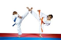 Τα υψηλά πόδια λακτισμάτων δύο αθλητές εκπαιδεύουν στο κόκκινο και μπλε χαλί Στοκ φωτογραφία με δικαίωμα ελεύθερης χρήσης