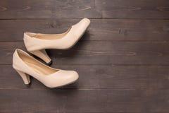 Τα υψηλά τακούνια είναι στο ξύλινο υπόβαθρο με το διάστημα αντιγράφων Στοκ Εικόνα